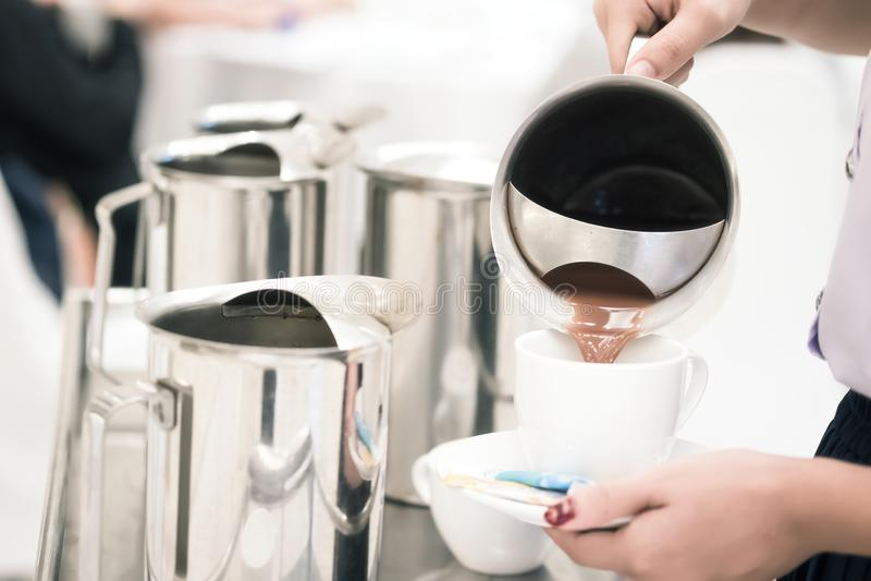 o pessoal da mulher está derramando o leite de chocolate no potenciômetro para servir os convidados ATT imagens de stock royalty free