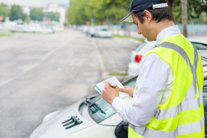 O pessoal do agente da polícia do estacionamento pune o carro erradamente estacionado imagens de stock