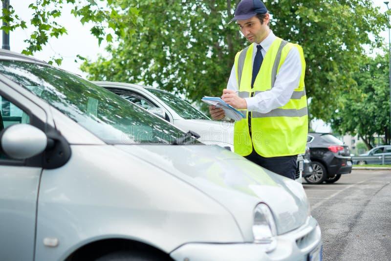 O pessoal do agente da polícia do estacionamento pune o carro erradamente estacionado fotos de stock