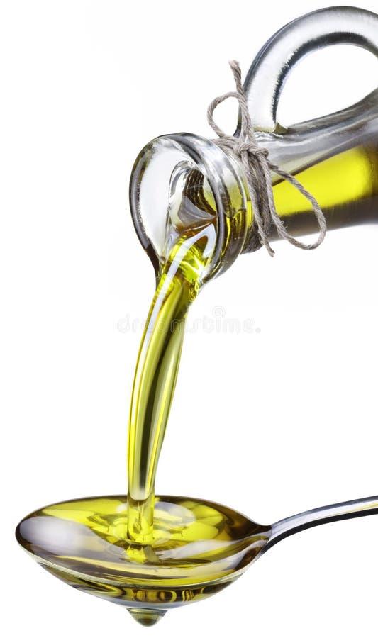 O petróleo verde-oliva derramou de um frasco em uma colher do metal. foto de stock