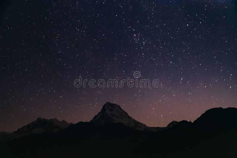 O pico da neve da montanha de Annapurna na noite com protagoniza nos Himalayas em Nepal imagens de stock