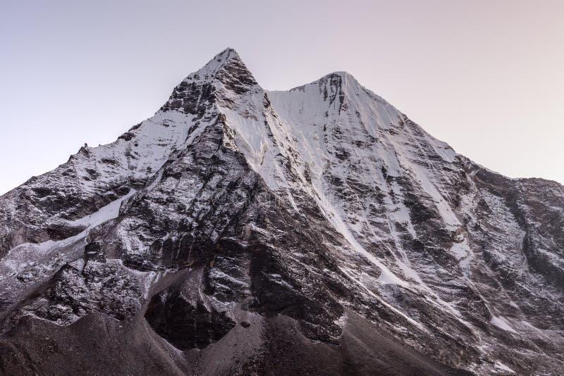 O pico de montanha bonito na neve iluminou-se pelo rosa fotos de stock royalty free