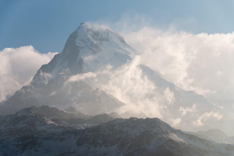 O pico de montanha muito alto da neve sobre as nuvens nivela imagens de stock