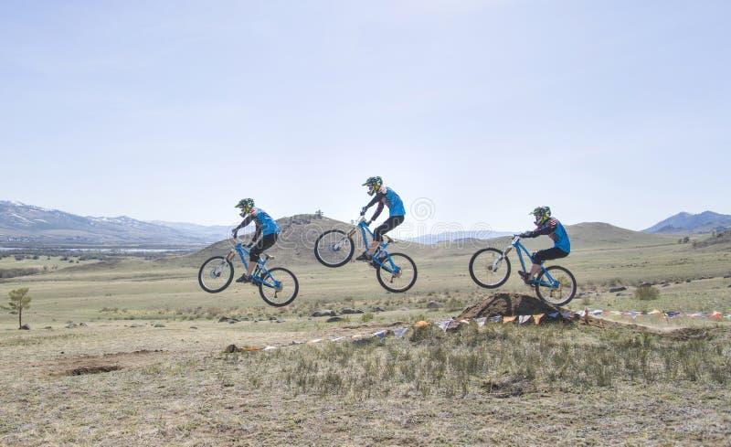 O piloto não identificado supera o salto na competição para o ' Copo de Buriácia em um Mountain bike imagem de stock royalty free