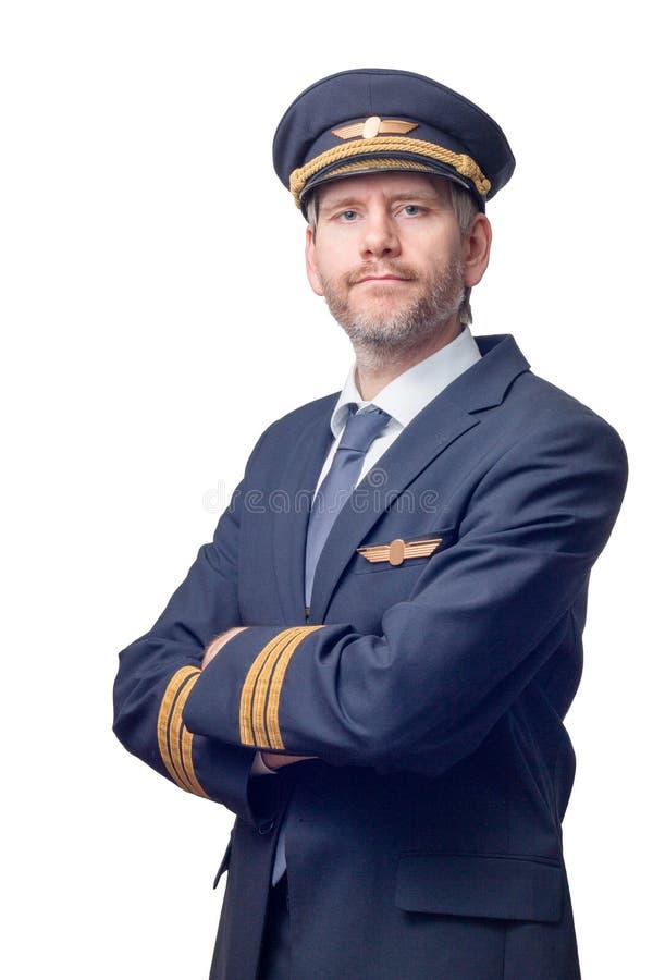 O piloto no uniforme com listras douradas e no tampão cruzou seus braços imagens de stock royalty free
