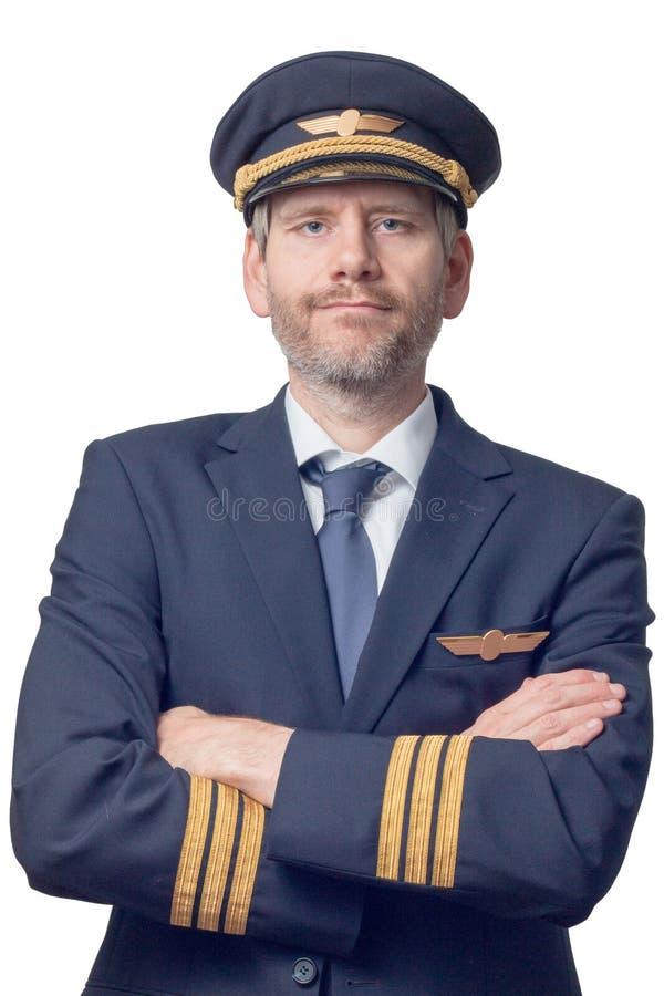 O piloto no uniforme com listras douradas e no tampão cruzou seus braços foto de stock