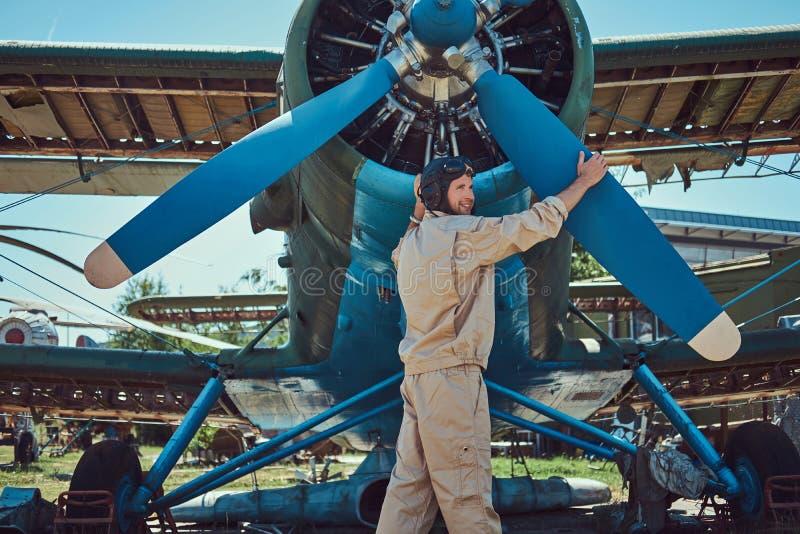 O piloto ou o mecânico em uma engrenagem completa do voo verificam a hélice de seu avião militar retro antes de um voo foto de stock royalty free