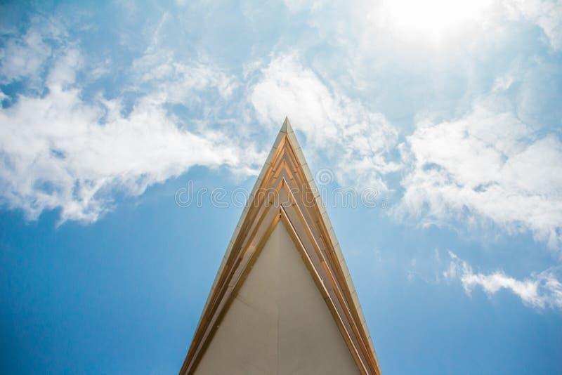 O pináculo afiado da construção corta completamente as nuvens fotos de stock