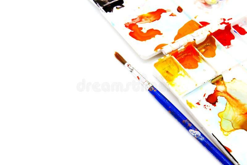 O pincel azul e a paleta branca sejam cor de água manchada isolados no fundo branco imagem de stock royalty free