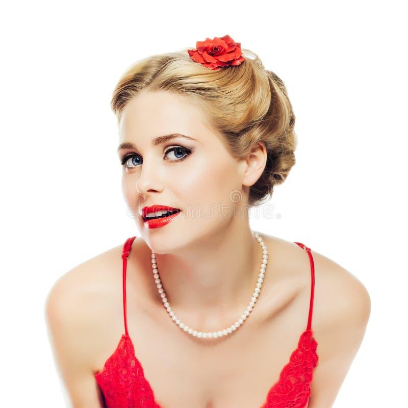 O pino-acima louro da menina no vestido do laço e na colar vermelhos da pérola olha playfully na câmera isolada no fundo branco imagem de stock