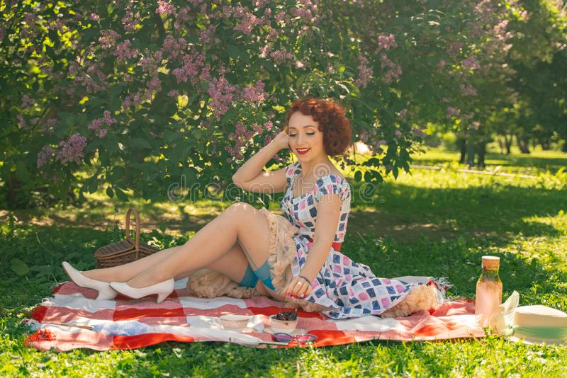 O pino feliz ruivo acima da menina no vestido do verão do vintage e das meias clássicas com uma emenda na parte traseira senta-se fotos de stock royalty free