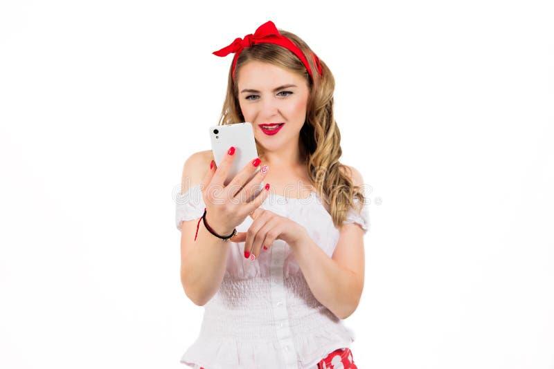 O pino retro bonito, atrativo da mulher de negócio da menina acima do estilo que joga no telefone celular isolou a parede branca  fotografia de stock