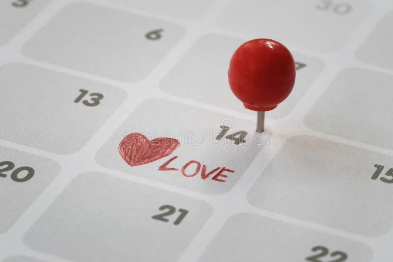 O pino vermelho pôs sobre o fundo em número quatorze do calendário imagens de stock royalty free