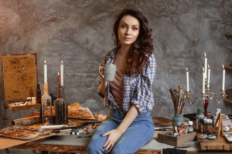 O pintor bonito novo da menina com uma xícara de café senta-se na tabela na oficina Antes do trabalho reflete em imagens para imagens de stock royalty free