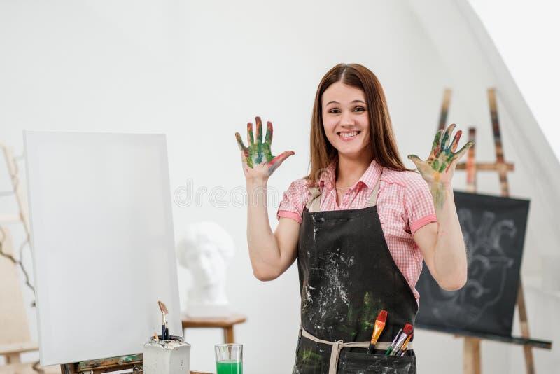 O pintor bonito novo da menina em um estúdio branco com palmas sujas mostra a classe, ri e exulta-a foto de stock
