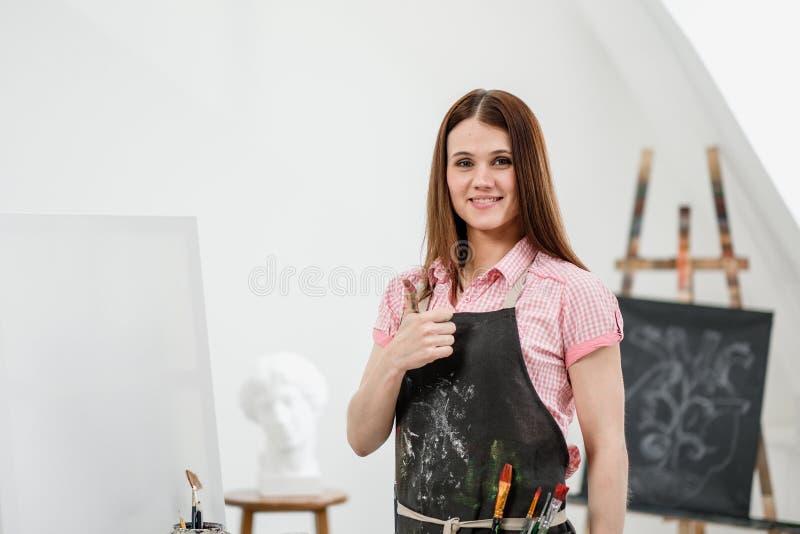 O pintor bonito novo da menina em um estúdio branco com palmas sujas mostra a classe, ri e exulta-a imagens de stock royalty free