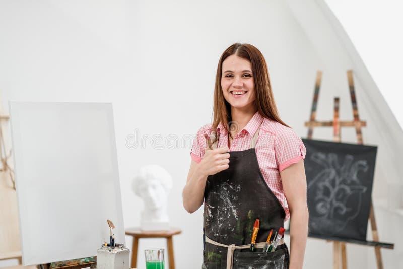 O pintor bonito novo da menina em um estúdio branco com palmas sujas mostra a classe, ri e exulta-a imagens de stock