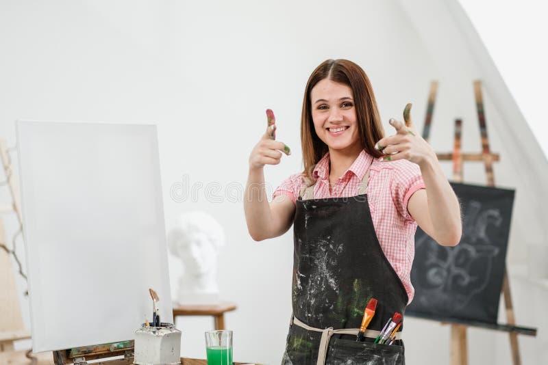 O pintor bonito novo da menina em um estúdio branco com palmas sujas mostra a classe, ri e exulta-a imagem de stock royalty free