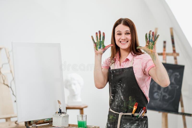 O pintor bonito novo da menina em um estúdio branco com palmas sujas mostra a classe, ri e exulta-a foto de stock royalty free