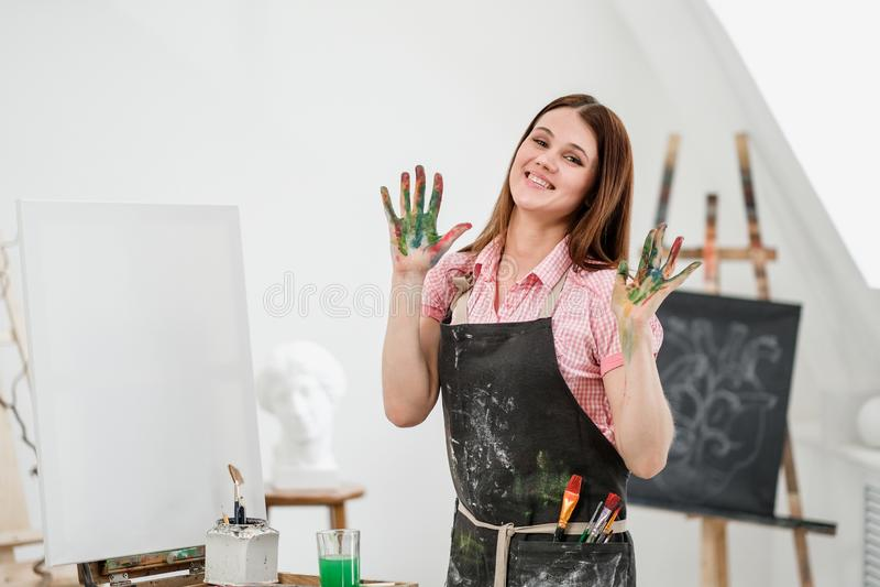 O pintor bonito novo da menina em um estúdio branco com palmas sujas mostra a classe, ri e exulta-a fotografia de stock