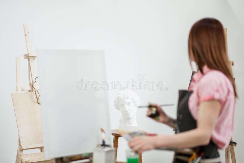 O pintor bonito novo da menina em um estúdio branco tira em uma armação na lona fotografia de stock
