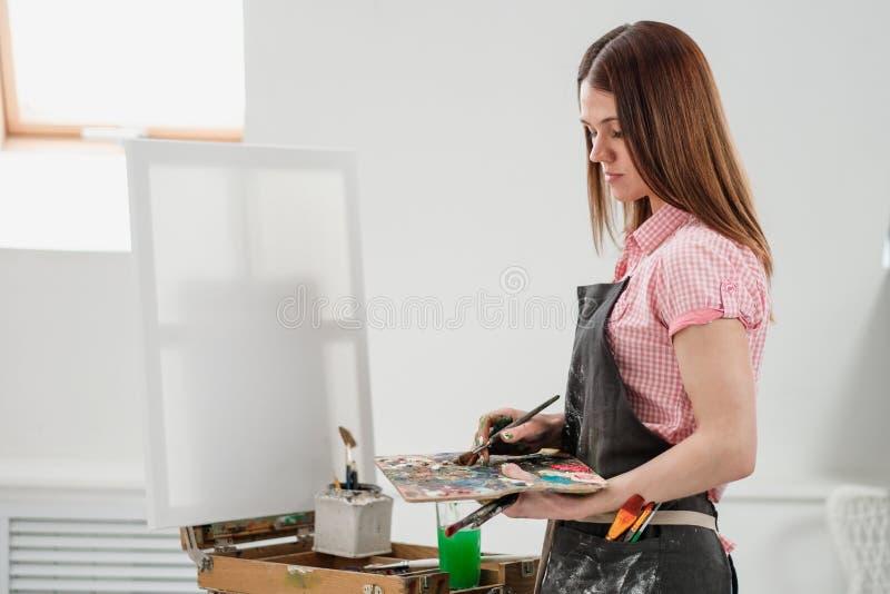 O pintor bonito novo da menina em um estúdio branco tira em uma armação na lona imagens de stock royalty free