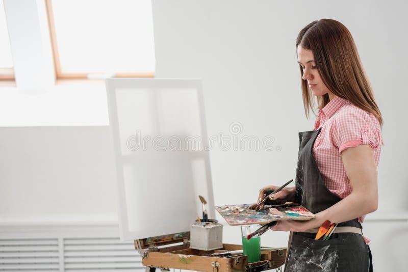O pintor bonito novo da menina em um estúdio branco tira em uma armação na lona imagem de stock royalty free