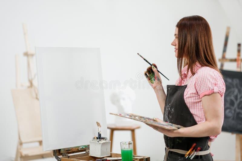 O pintor bonito novo da menina em um estúdio branco tira em uma armação na lona imagens de stock