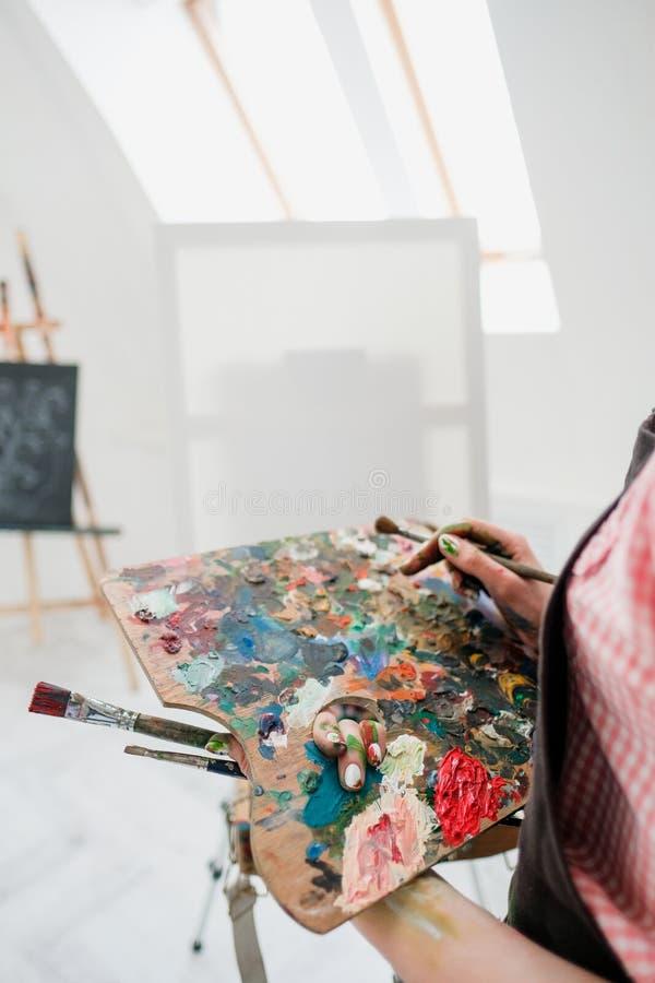 O pintor bonito novo da menina em um estúdio branco tira em uma armação na lona fotos de stock royalty free