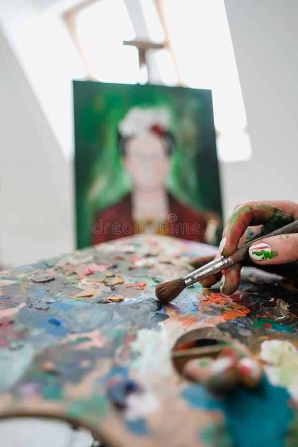 O pintor bonito novo da menina em um estúdio branco tira em uma armação na lona foto de stock royalty free