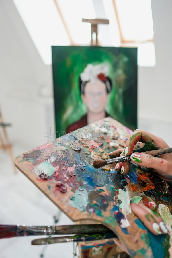 O pintor bonito novo da menina em um estúdio branco tira em uma armação na lona foto de stock