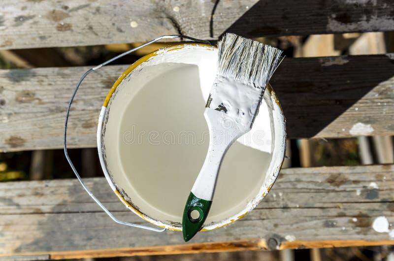 O pintor com uma escova e um frasco da pintura branca est? preparando-se para pintar a casa, parede, constru??o fotografia de stock royalty free