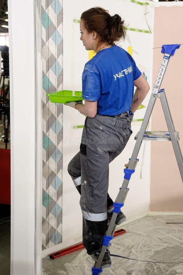 O pintor fêmea decora a parede, executando a tarefa fotografia de stock