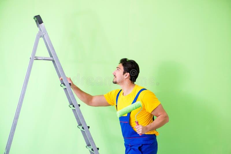 O pintor novo que faz a renovação em casa fotografia de stock
