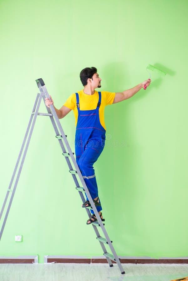 O pintor novo que faz a renovação em casa fotos de stock royalty free