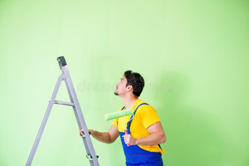 O pintor novo que faz a renovação em casa foto de stock royalty free