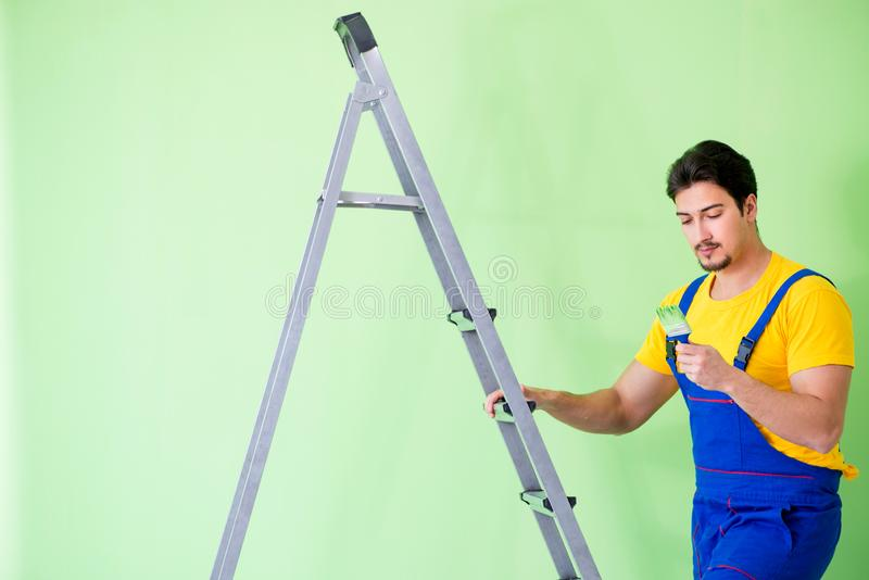 O pintor novo que faz a renovação em casa fotos de stock