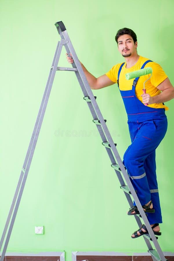 O pintor novo que faz a renovação em casa imagem de stock