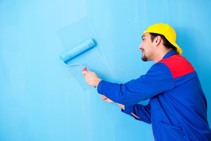 O pintor novo que faz a renovação em casa foto de stock