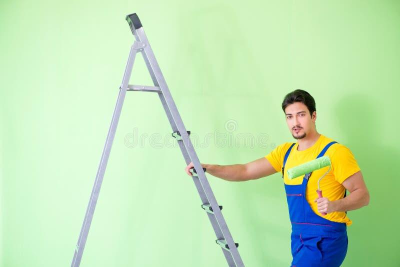 O pintor novo que faz a renovação em casa imagens de stock