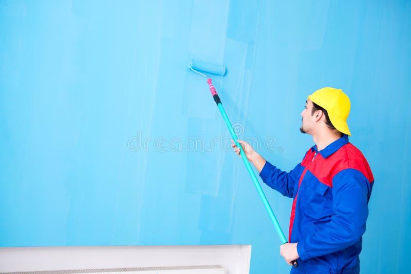 O pintor novo que faz a renovação em casa imagens de stock royalty free