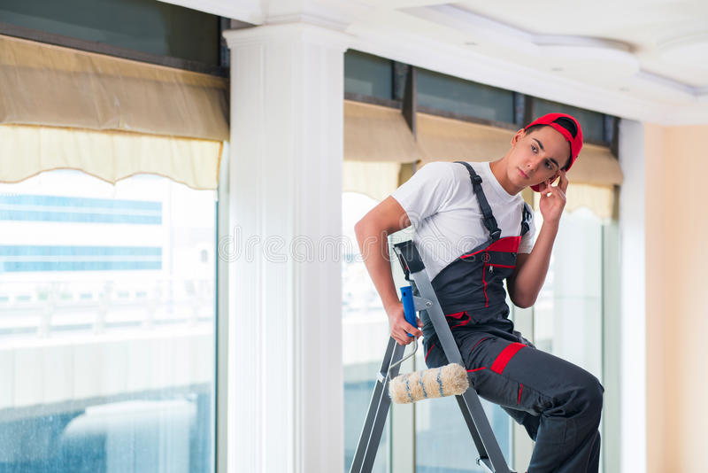 O pintor novo que pinta o teto no conceito da construção imagem de stock royalty free