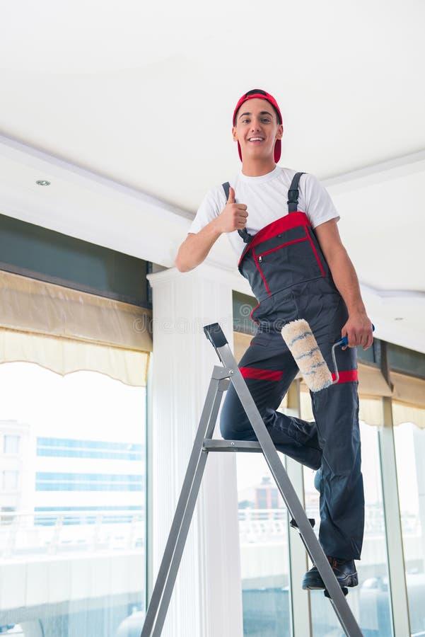 O pintor novo que pinta o teto no conceito da construção foto de stock royalty free