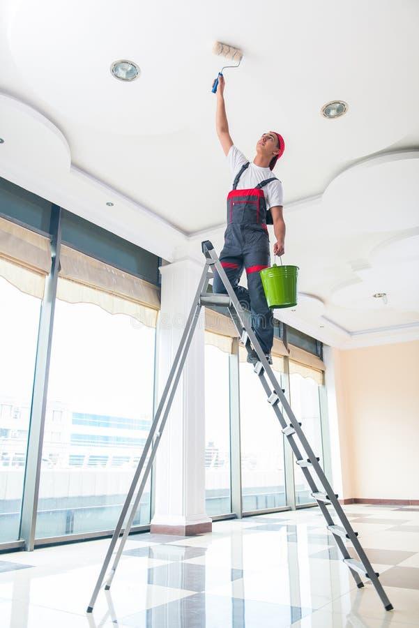 O pintor novo que pinta o teto no conceito da construção fotos de stock