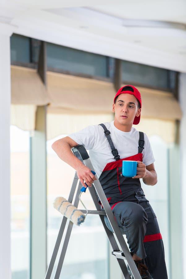 O pintor novo que pinta o teto no conceito da construção foto de stock