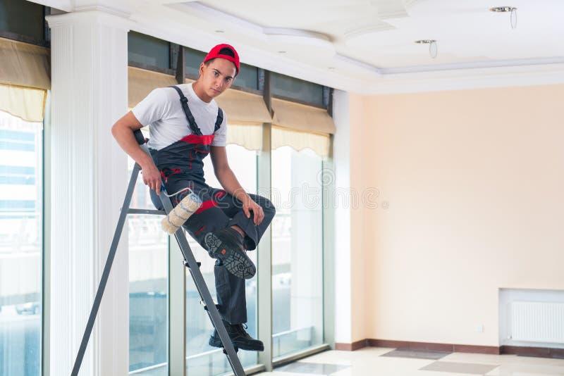O pintor novo que pinta o teto no conceito da construção imagem de stock
