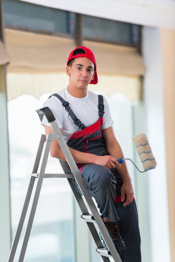 O pintor novo que pinta o teto no conceito da construção fotografia de stock royalty free
