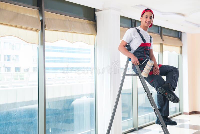 O pintor novo que pinta o teto no conceito da construção imagens de stock