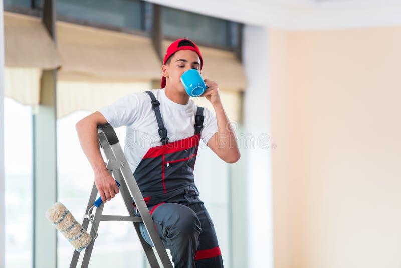 O pintor novo que pinta o teto no conceito da construção imagens de stock royalty free