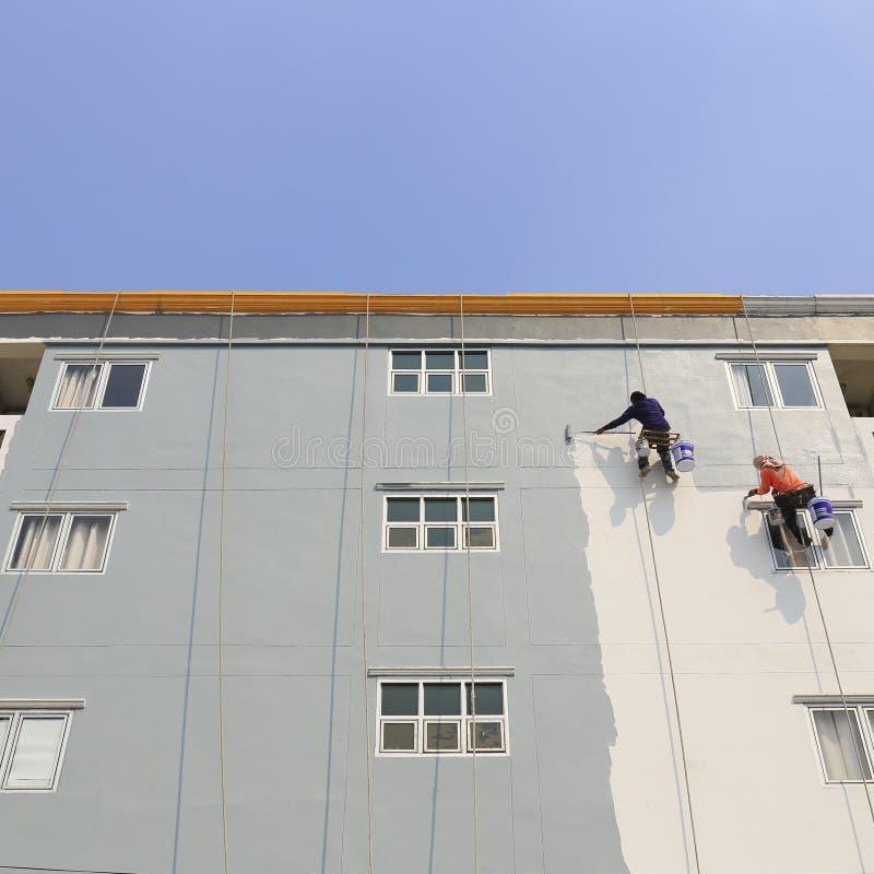 O pintor usa um rolo de pintura fora da construção alta fotos de stock